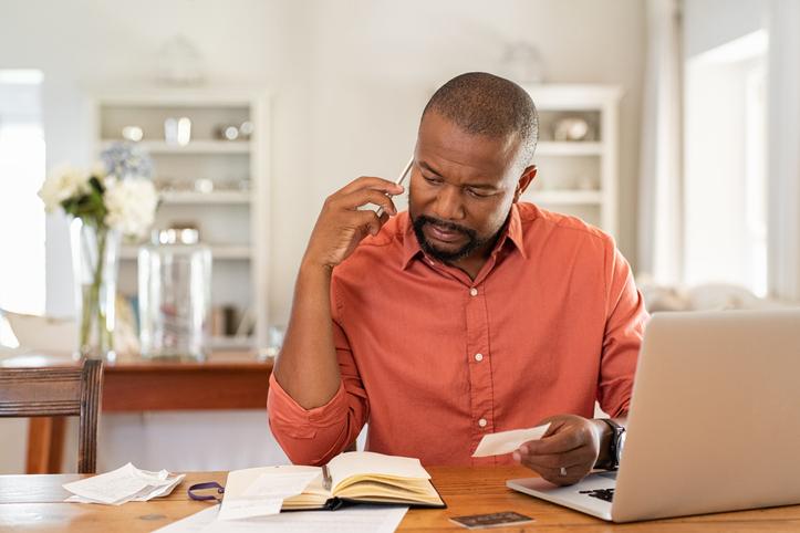 man at desk reviewing debt